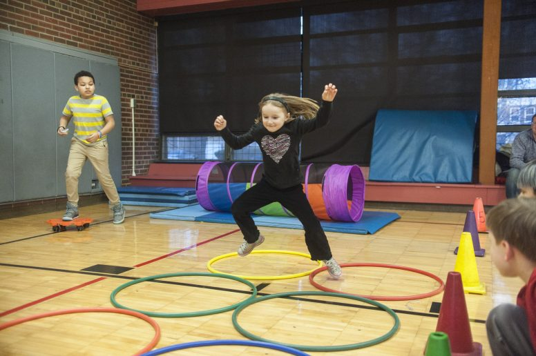 "Sonia Peterson uses some fancy footwork to navigate rows of hula hoops that were part of an obstacle course at Blythe Park School's ""One School, One Book"" event on Thursday, March 16. 
