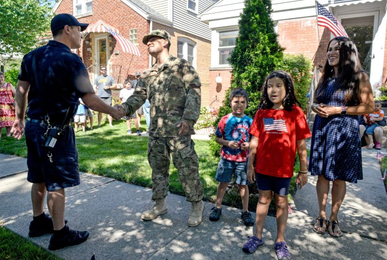 Firefighter paramedic Brad Pacyga, left, shakes hands with Air Force veteran Alex Leon, with his children Nicholas, 6, and Natalia, 9, and his wife Alma on Saturday, July 29, during a surprise recognition parade for Alex outside of his home in Brookfield. He recently returned home from being overseas. | Alexa Rogals/Staff Photographer