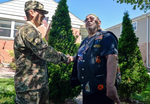 Alex Leon shakes hands with VFW Post 2868 Commander Julius Torrentt outside on Alex's home. Torrentt and other VFW members, along with the Brookfield Fire and Police Departments, got together to welcome Alex home after returning from overseas. | Alexa Rogals/Staff Photographer