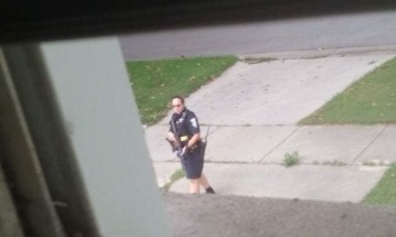 A police officer armed with a rifle searches 8th Avenue for the man suspected of sexually assaulting a North Riverside woman on the morning of Aug. 6. (Photo courtesy of Ben Brundage Jr.)