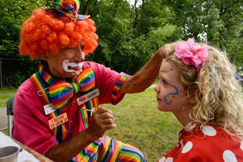 Rudi Kazoodi the clown paints a design on Hannah Dittrich, 7, of Lombard, during the 101st Annual Scottish Home Picnic in North Riverside on Aug. 5. The picnic had different children's events like face painting, arts and crafts and Highland dancers. | Alexa Rogals/Staff Photographer