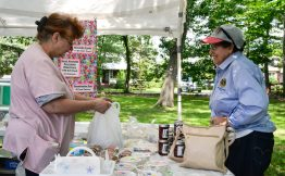 Mary Maguire, director of housekeeping for the home, sells a blueberry cake to Maria Fernandez, of Berwyn at the 101st Annual Scottish Home Picnic in North Riverside on Aug. 5. | Alexa Rogals/Staff Photographer