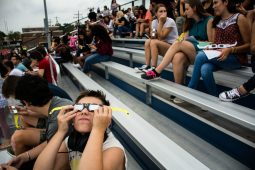A Riverside-Brookfield High School student looks up with solar glasses to view the eclipse on Monday. | Sebastian Hidalgo/Contributor