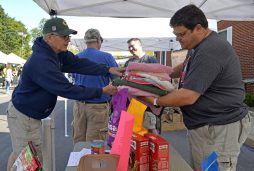 Wayne Valentino hands a bundle of towels to Brookfield Village Manager Keith Sbiral on Sept. 2 at the village's farmers market, where Sbiral and other staff members collected items and cash donations that will be taken to Houston to help animal victims of Hurricane Harvey. | Alexa Rogals/Staff Photographer