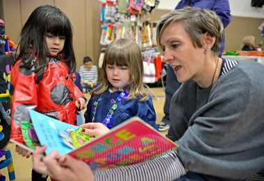 Rachel Harris, an education leader with Discovery Toys, reads a children's book to Adria Mercado, 4, of North Riverside, and Sydney Norman, 4, of Bellwood, on Nov. 4, during the annual Holiday Bazaar at the Village Commons on Des Plaines Avenue in North Riverside. | Alexa Rogals/Staff Photographer