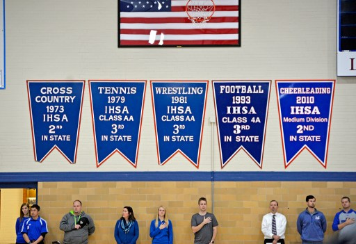 Faculty members stand for the Pledge of Allegiance on Nov. 10, during the annual Veteran's Day assembly inside the gymnasium at Riverside Brookfield High School. | Alexa Rogals/Staff Photographer