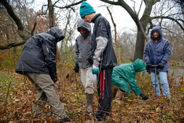 A rainy day kept the number of volunteers a bit lower for the annual 1,000 Tree Planting Project in Riverside on Nov. 18, but it didn't deter this group of kids who lugged a jug of tree seeds through the woods in order to plant them near the Des Plaines River. Above left, (from left) Mateo Cubas, Zack Hosek and Steven Sanduski team up to plant one of the many tree seeds. | Alexa Rogals/Staff Photographer