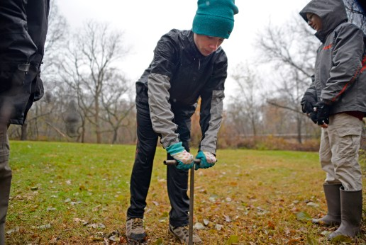 Steven Sanduski of Riverside, bores a hole in the soil in a wooded area near the Des Plaines River in Riverside to plant a seed during a rain-soaked edition of the annual 1,000 Tree Planting Project on Nov. 18. | Alexa Rogals/Staff Photographer