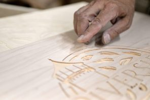 Woodworker Paul Meyer points out how the Riverside logo was etched into an oak panel that became part of the village board's main council table. | Alexa Rogals/Staff Photographer