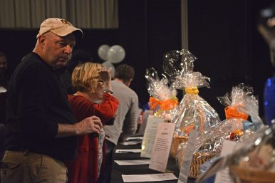 Attendees look over the different packages in the silent auction on Jan. 28, during the Riverside Winter Hootenanny at Beyond Words Dance Center.   Alexa Rogals/Staff Photographer