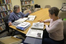 Debbie Valentino and Lynn Daugherty, both of Brookfield, plow through binders of historic photos, researching the subject matter and writing labels before the pictures are scanned into a Brookfield Public Library database. | Alexa Rogals/Staff Photographer