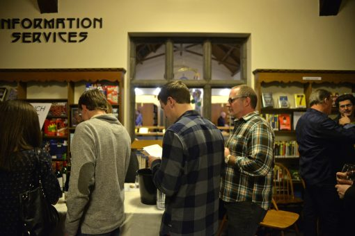 Attendees wait in line near the Information Services desk to sample some wine on Feb. 3 during the Between The Wines fundraiser event at Riverside Public Library. | Alexa Rogals/Staff Photographer