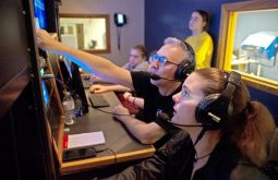 RBTV supervisor Gary Prokes (pointing) and program alumna Staci Sherman discuss finer points of broadcast production while students Charles and Sara Vacek observe during the 2018 Riverside Brookfield Educational Foundation telethon on March 10 at Riverside-Brookfield High School. | Alexa Rogals/Staff Photographer