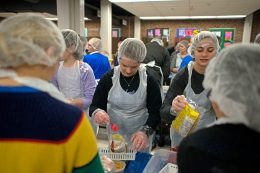 Volunteers fill up the bags of food with macaroni noodles during a Feed Our Community event on April 14 in conjunction with the Hauser Junior High School food drive, sponsored annually by the school's PTO. | Alexa Rogals/Staff Photographer