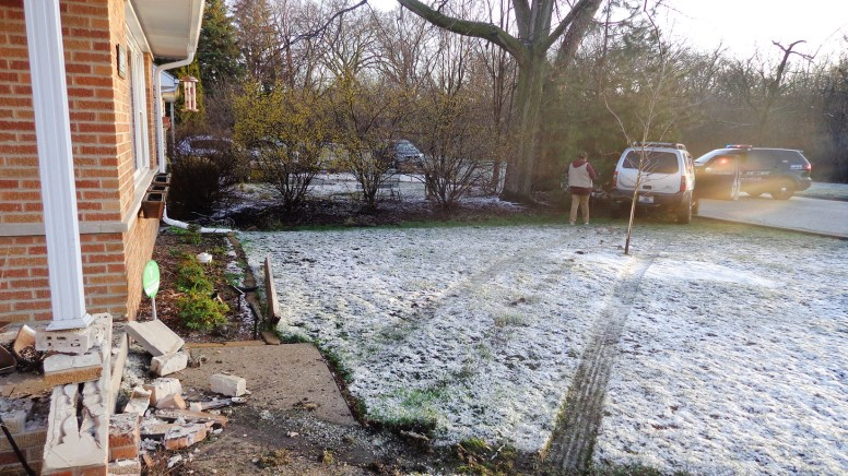 A Nissan Xterra driven by a Chicago woman jumped the curb and struck the house at 31st Street and Forest Avenue after the SUV hit a patch of ice while crossing the Salt Creek Bridge. Similar conditions resulted in another vehicle hitting the same house back in December 2011. (Photo courtesy of the Brookfield Police Department)