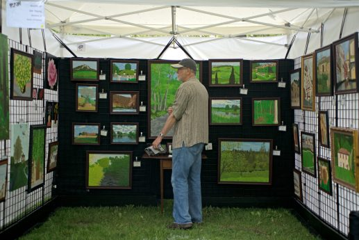 Oil painter Jim Young, of Aurora, looks through the art pieces he has in his booth on May 19, during the annual Riverside Arts Weekend, at Guthrie Park in Riverside. | Alexa Rogals/Staff Photographer
