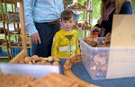 5-year-old Ryan Bradford of Riverside gets a closer look at wooden toys exhibited by John Post on May 19, during the annual Riverside Arts Weekend, at Guthrie Park in Riverside. | Alexa Rogals/Staff Photographer