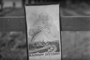 Those paying respects to the 42nd Division's dead at the military cemetery in Baccarat on Decoration Day, May 30, 1918, hung small pictures bearing the division's name, its rainbow insignia and an American flag.   U.S. Army Signal Corps movie still, courtesy of National Archives