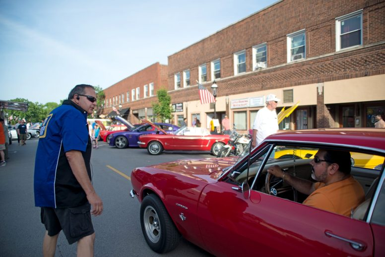 Rick Rovella (above, left) guides a classic car enthusiast down East Burlington Street in downtown Riverside on June 7 at the start of the Chamber of Commerce's first Cruise Night of the summer. Future Cruise Nights will be held July 12 and Aug. 9. | Alexa Rogals/Staff Photographer