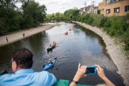 Onlookers watch over the kayakers as they paddle their way under the swinging bridge on July 28, during the 2nd annual Scuff Gross Memorial Riverside Regatta on the Des Plaines River. | Alexa Rogals/Staff Photographer