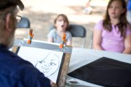 David Curbis paints a caricature of Grace Jolie, 4, left, and her sister Kate Jolie, 11, of Oak Park, on Aug. 4, during the 102nd annual picnic at the Caledonia Senior Living and Memory Care in North Riverside. | Alexa Rogals/Staff Photographer