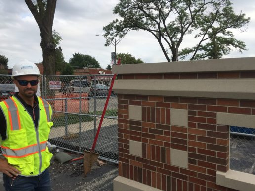 Project superintendent Tom Thies shows off a sample precast wall panel, which incorporates a brick and concrete veneer that mimics S.E. Gross Middle School's historic look. (Bob Uphues | Staff)