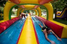 Neighborhood kids race each other on the blow up slip-n-slide on Aug. 18, during the Maplewood Road 30th annual block party in Riverside. | Alexa Rogals/Staff Photographer