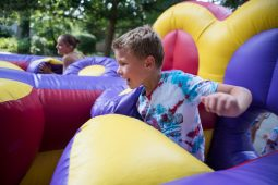 Residents race each other in a bounce house jungle gym on Aug. 18, during the Maplewood Road 30th annual block party in Riverside. | Alexa Rogals/Staff Photographer