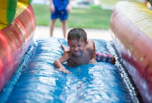 Kids from the block race each other on the inflatable slip-n-slide on Aug. 18, during the Maplewood Road 30th annual block party in Riverside. | Alexa Rogals/Staff Photographer