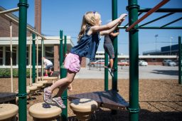 Sonia Knapp jumps off a platform and grabs onto the monkey bars on Aug. 23, during a teddy bear picnic after the first day of kindergarten at Hollywood Elementary School in Brookfield. | Alexa Rogals/Staff Photographer