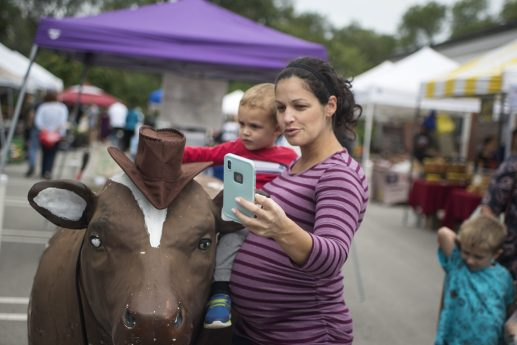 Tammy Miller, of Brookfield, takes a selfie with her son, Sebastian, 2, in front of the Brookfield Restaurant - soon to be the Tony's Restaurant - cow at the Brookfield Farmers Market on Page 8. The cow will get a new paint job before going back to its longtime home on the roof at 8900 Ogden Ave. | Alexa Rogals/Staff Photographer