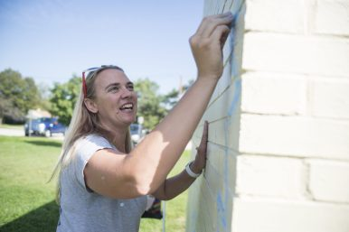 Jessie Tamburello uses chalk to make a quick outline of the mural going up this week, at Elhert Park in Brookfield. | Alexa Rogals/Staff Photographer