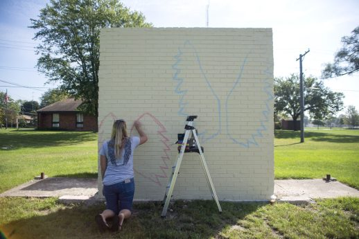 Jessie Tamburello outlines where the wings are planned to go on the mural on Sept. 14, at Elhert Park in Brookfield. | Alexa Rogals/Staff Photographer