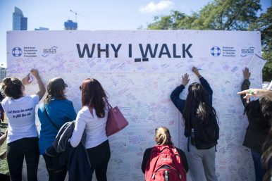 Walkers sign and write the reasons why they walk on a wall on Sept. 22, during the American Foundation for Suicide Prevention Out of the Darkness Walk at Grant Park in Chicago. | Alexa Rogals/Staff Photographer
