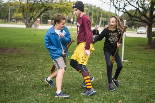 From left, Mason Myslinski, Loyola University student Parker Harris and Natalie Grover run around the field on brooms on Sept. 29, during Quidditch outside of the North Riverside Village Commons on Des Plaines Avenue. | Alexa Rogals/Staff Photographer