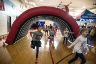 A group makes their way under an inflatable tunnel on Oct. 5, during the walkathon inside the gymnasium at Congress Park School in Brookfield. | Alexa Rogals/Staff Photographer