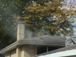 Fort-five minutes after the firefighters responded to the scene, smoke could still be seen escaping 3815 Madison Ave. through openings in the roof. (Bob Uphues | Staff)