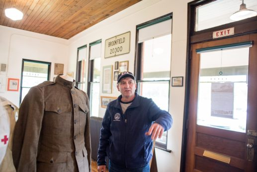 Kit Ketchmark stands next to an old military uniform on Oct. 26, at the Grossdale Station Museum in Brookfield. | ALEXA ROGALS/Staff Photographer