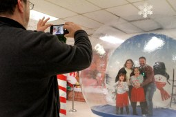 Brookfield special events commissioner David Harazin takes a photo of the Buscemi family, Julie and Jeff with kids Hannah and Olivia, inside an inflatable snow globe at the Brookfield Village Hall during a very rainy village-wide holiday celebration on Dec. 1. | Photo by Sarah Minor