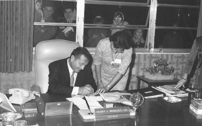Tony Martin signs a slip opening an honorary account at the bank while fans gawk through the windows of savings and loan President Henry Moravec Sr.'s ground-floor office. | Photo courtesy Liz Faron collection