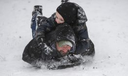 Emmett Schiemann, left, 4, and Edward Angarita, both of Riverside, sled down a hill together on Jan. 12, at Swan Pond in Riverside. | Alexa Rogals/Staff Photographer