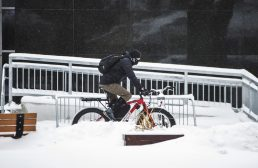 A cyclist rides through the snow on Jan. 19, in front of Riverside Brookfield High School in Riverside. | ALEXA ROGALS/Staff Photographer