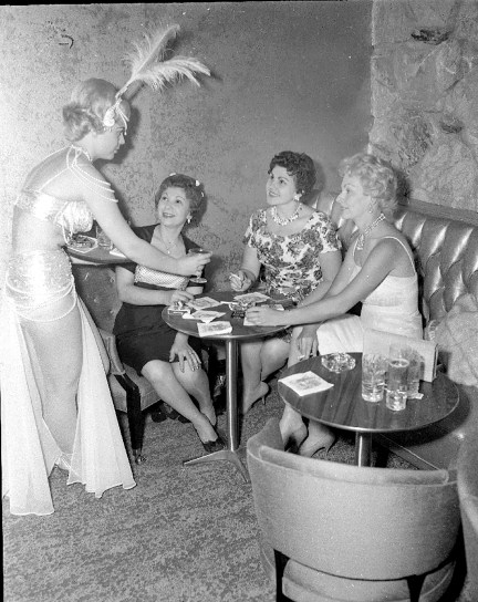 """A scantily-dressed """"harem girl"""" cocktail waitress serves drinks at the Sahara North. (Courtesy Liz Faron collection)"""
