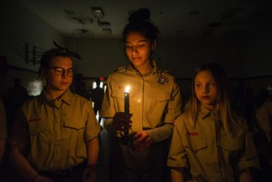 McKenzie Monahan (from left), Joanna Vera and Laura Geisert pass a candle to one another during their induction ceremony into Troop 90 on Feb. 27 at Brook Park School in LaGrange Park. | Alexa Rogals/Staff Photographer