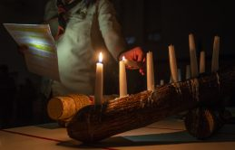 Scoutmaster Jessie Tamburello lights candles on Feb. 27, during an induction ceremony for the Boy Scouts of America Troop 90GT at Brook Park Elementary School in La Grange Park. | ALEXA ROGALS/Staff Photographer