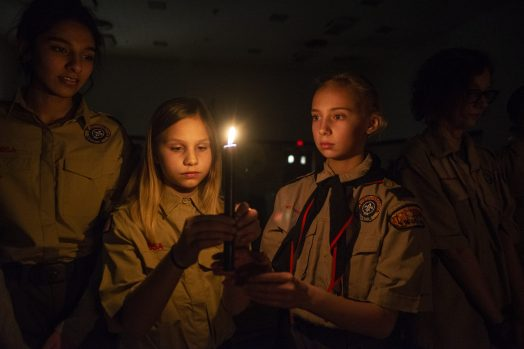 Laura Geisert, left, and Ella Tamburello, both 11, pass the candle on Feb. 27, during an induction ceremony for the Boy Scouts of America Troop 90GT at Brook Park Elementary School in La Grange Park. | ALEXA ROGALS/Staff Photographer