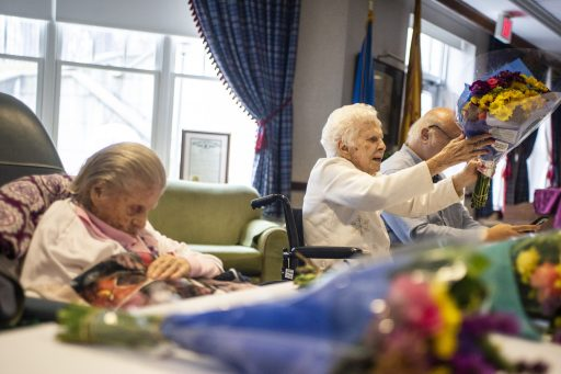 Gladys Strunfield receives a bouquet of flowers on March 21, during a birthday celebration for residents who turned 100 and over at Heritage Hall at Caledonia Senior Living and Memory Care in North Riverside. | ALEXA ROGALS/Staff Photographer