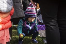 A toddlers picks up a plastic egg during the Riverside Parks and Rec's annual Easter Egg Hunt at Big Ball Park on April 13. | Alexa Rogals/Staff Photographer