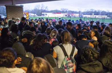 Students huddle together and comfort each other during a community prayer outside of the front entrance of George Washington Middle School. | ALEXA ROGALS/Staff Photographer