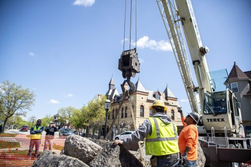 Workers from F.H. Paschen guide a crane lifting a section of the Driver Monument from the ground after it tumbled earthward into three pieces when a strap securing the granite horse trough broke while lifting it onto a new concrete footing in Guthrie Park on May 13. | Alexa Rogals/Staff Photographer